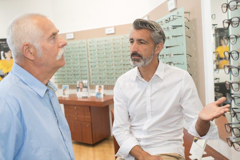 Opticien montrant des lunettes de gamme au client photographie stock
