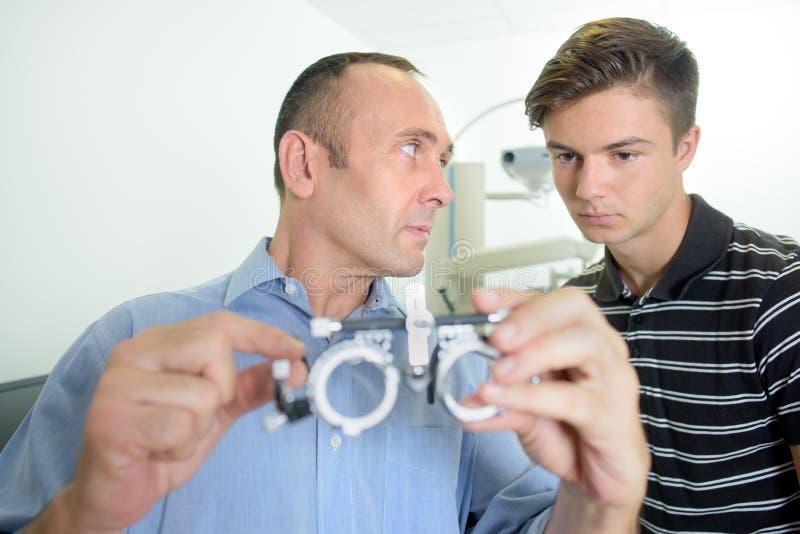 Opticien montrant les verres eyetest au stagiaire photographie stock