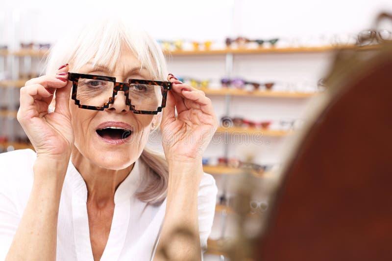 optiker En äldre kvinna i en optisk salong royaltyfria foton