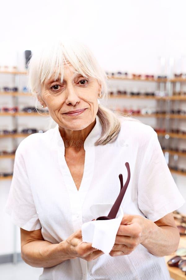 optiker En äldre kvinna i en optisk salong arkivbild