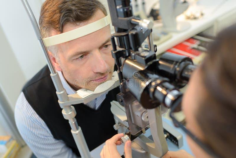 Optiker i kirurgi som ger manögonprovet arkivfoto
