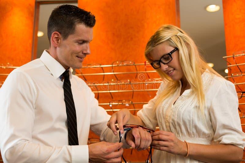 Optiker oder Optometriker, die einen Kunden über Brillen konsultieren lizenzfreies stockbild