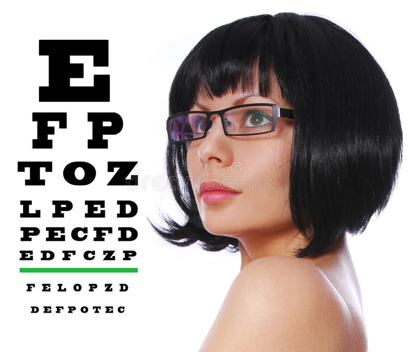 Optiker. Tragende Gläser des schönen Brunette Diagramm und Snellen-Augenuntersuchung lokalisiert auf Weiß stockbilder