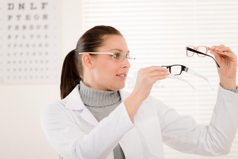 Optikerdoktorfrau mit Gläsern und Augendiagramm stockfoto