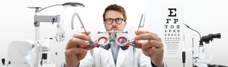 Optikerhänder med försökramen, optometrikerdoktor undersöker ögat arkivbild