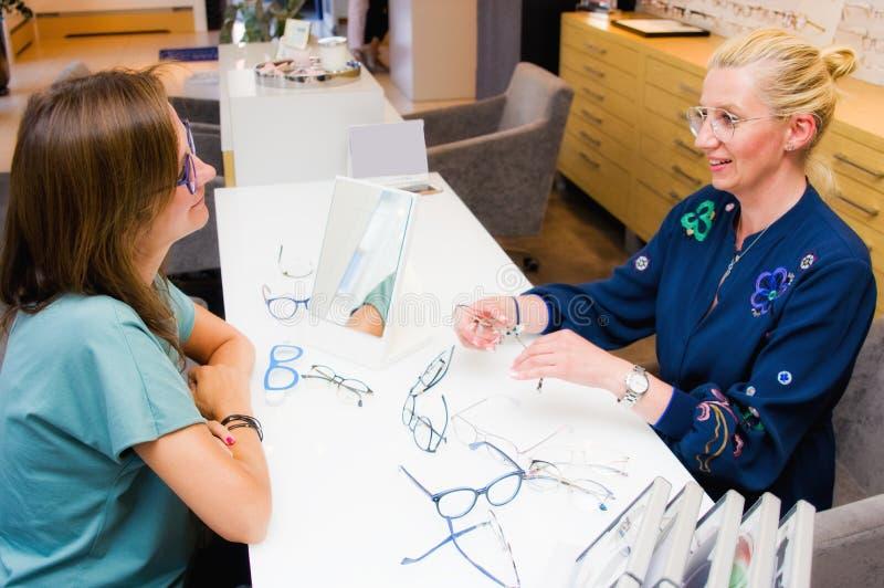 Optikersalonverkäuferin mit ihrem Kunden, der Brillen wählt stockbild