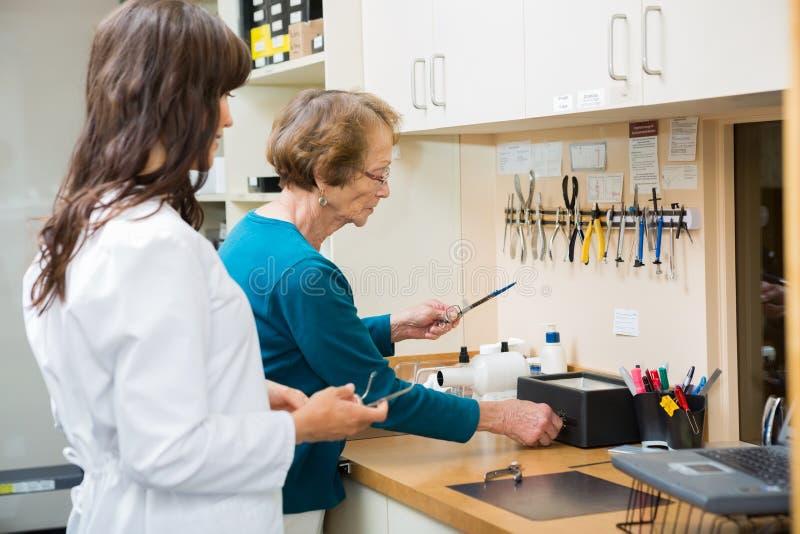 OptikerWith Apprentice Repairing exponeringsglas in arkivfoton