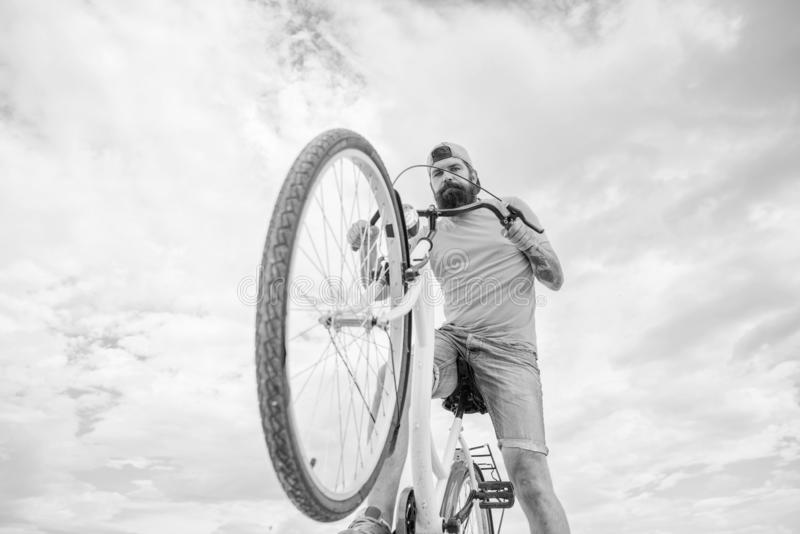 Optimera att cykla kapacitet Mannen uppsökte hipsterritter cyklar himmelbakgrund för den nedersta sikten Modern cykelridning arkivbilder