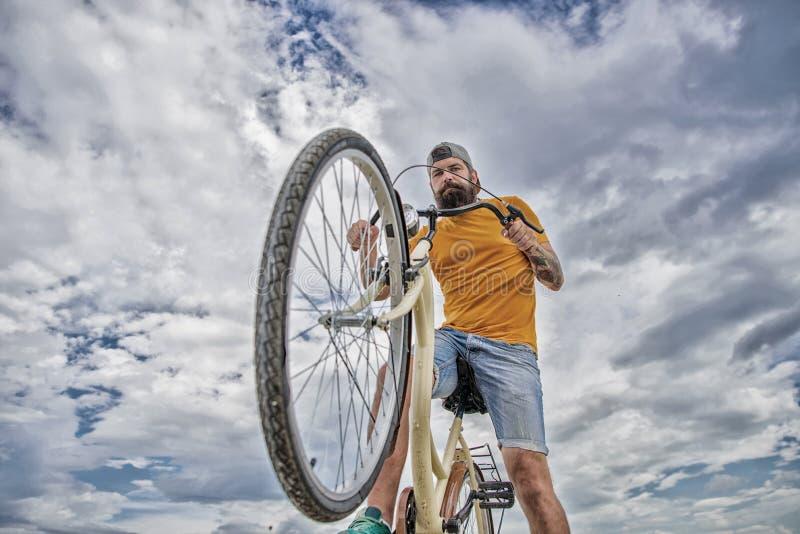 Optimera att cykla kapacitet Mannen upps?kte hipsterritter cyklar himmelbakgrund f?r den nedersta sikten Modern cykelridning arkivbilder