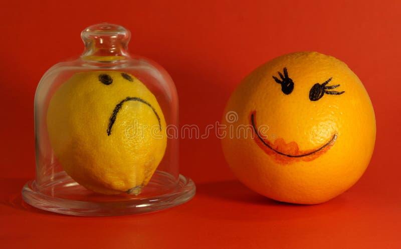 Optimism- och pessimismbegrepp citron med en ledsen smiley framsida och apelsin med en gladlynt smiley royaltyfri bild