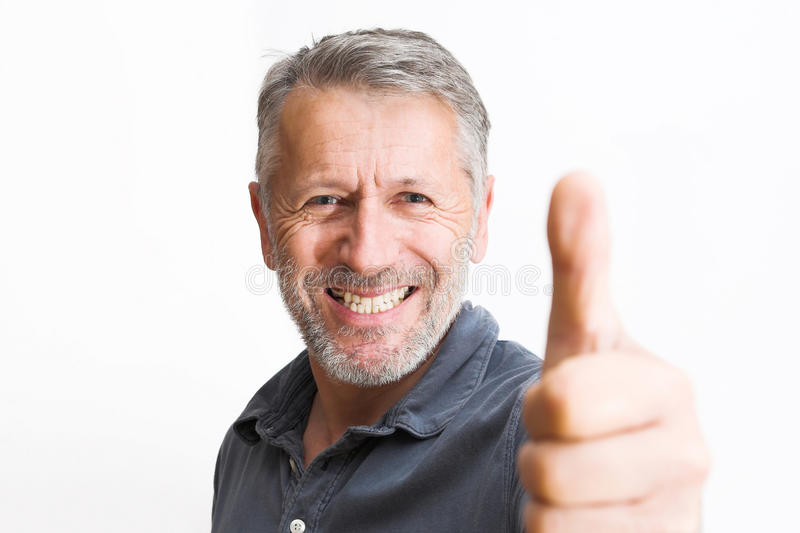 Optimist. Graying man rises his thumb with a wide, bright smile royalty free stock photos