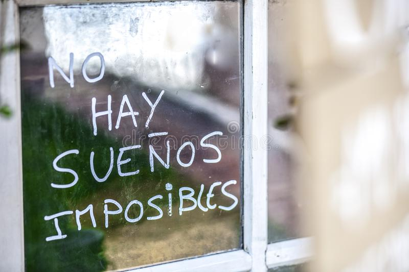 Optimist phrase written over old windows glasses in spanish. There are no impossible dreams traslation royalty free stock photography