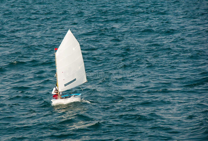 Optimist sailboat. Dinghy - training class yachts of the International Sailing Federation for the Children. Optimist sailboat during a training session in the stock photos