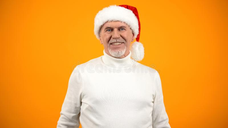 Optimistic aged man in Santa Claus hat smiling on camera, new year celebration stock photos