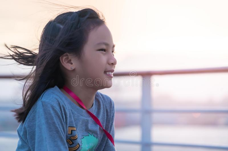 Optimistic female kid is looking out to the sea with sunset and smile. for Happiness and possitive life style concept royalty free stock photography