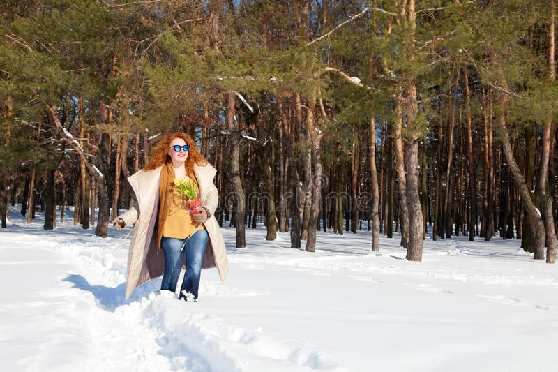 Smiling joyful woman walking through snowdrifts with forest on the background royalty free stock photography