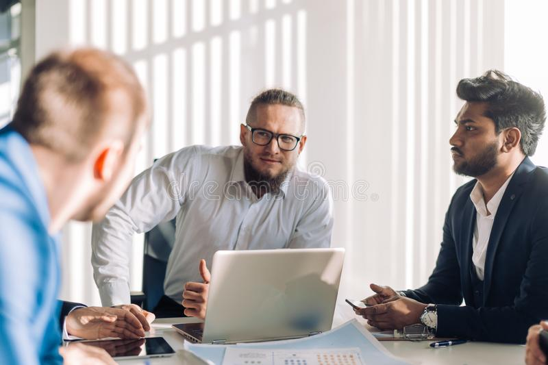 Optimistic businessman in white shirt collaborating with his team at meeting. Confident optimistic businessman in light blue shirt and his team. Caucasian stock images