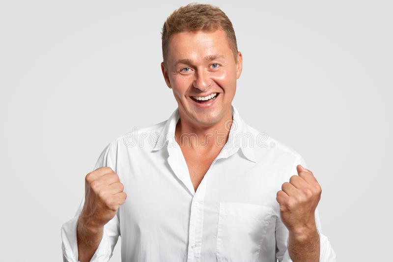 Optimistic cheerful European male clenches fists with triumph, celebrates his success at work, had friendly smile, dressed in whit. E shirt, poses indoor stock images