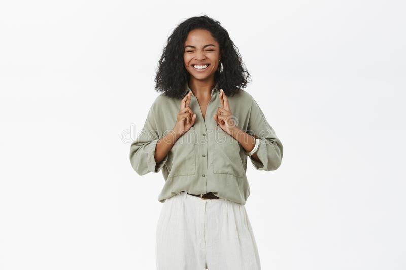 Optimistic hopeful good-looking happy and excited african american young new office worker in trendy outfit making wish royalty free stock photography