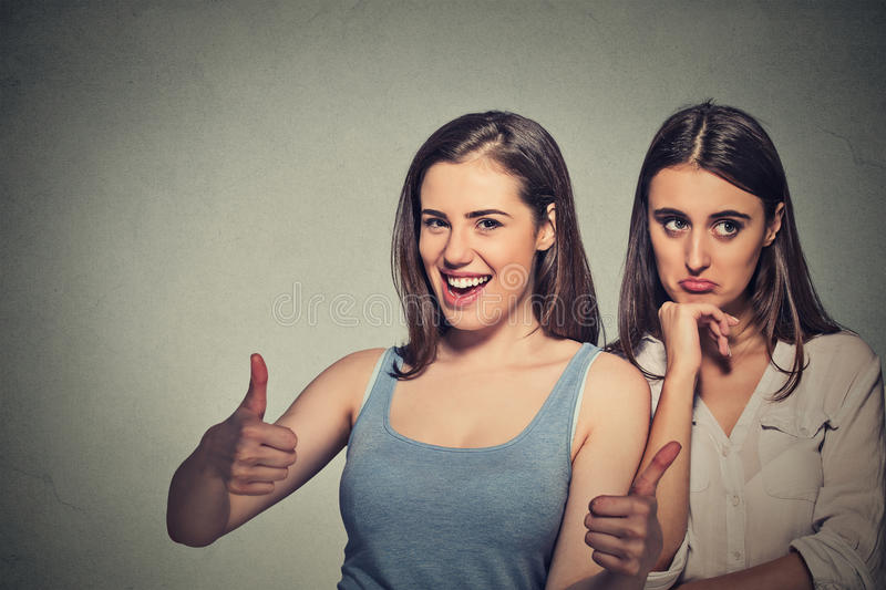 Optimistic lady having solution and bored, annoyed clueless sad woman royalty free stock images