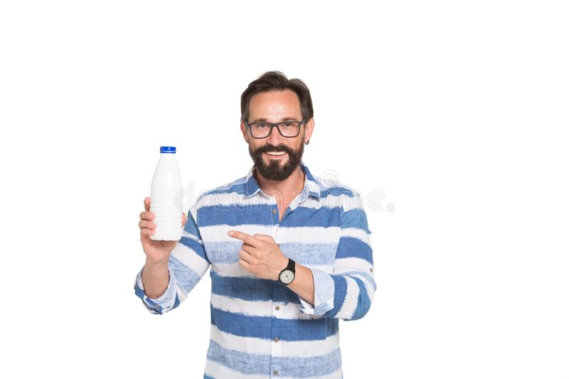 Optimistic mature man pointing at the bottle with fresh milk. Healthy lifestyle. Waist up of joyful bearded man wearing spectacles and looking at you with bright stock images