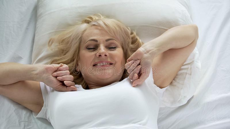 Optimistic middle-aged woman waking up early in morning, vitality and energy stock photography