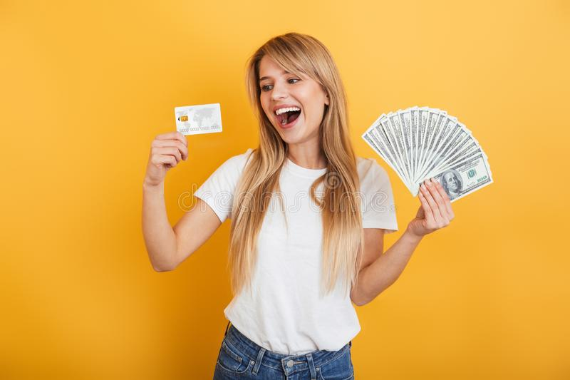 Optimistic positive young blonde woman jumping isolated over yellow wall background dressed in white casual t-shirt holding money. Image of optimistic positive royalty free stock photos