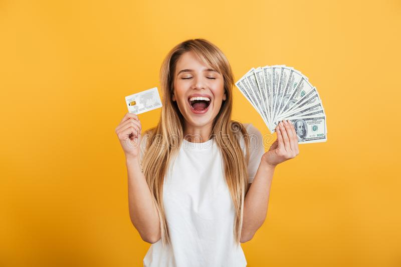 Optimistic positive young blonde woman jumping isolated over yellow wall background dressed in white casual t-shirt holding money. Image of optimistic positive stock photos