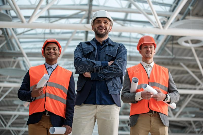 Optimistic skilled engineers are working on new project. Professional team. Low angle portrait of joyful young builders are standing together and looking ahead royalty free stock photo