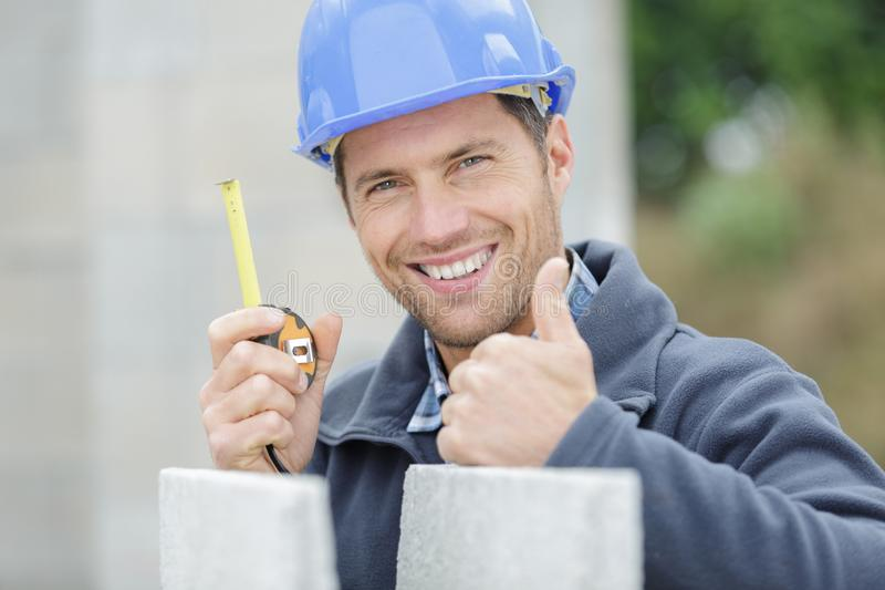 Optimistic worker builder shows thumb up stock photos
