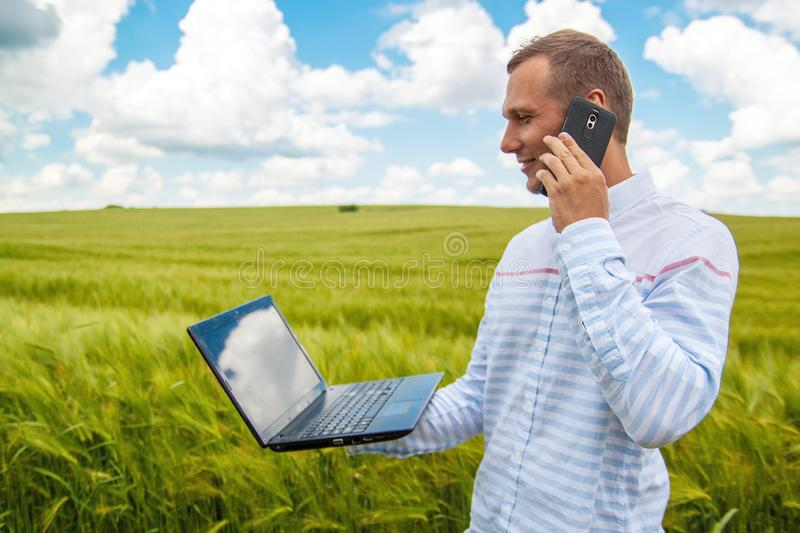 Businessman using laptop and smartphone in wheat field. royalty free stock photo