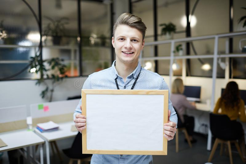 Optimistic young employee presenting information on banner royalty free stock images