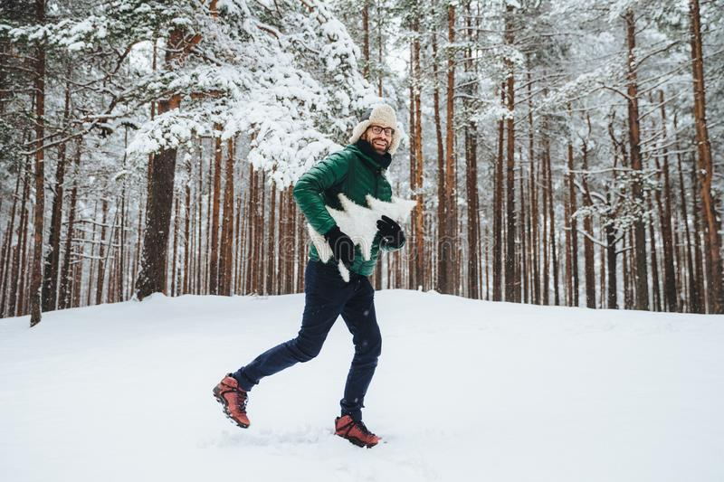 Optimistic young male dressed in warm winter clothes, has fun outdoor in winter forest, breath fresh air, glad to see much snow, h royalty free stock images