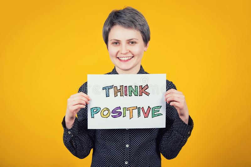 Optimistic young woman hipster holding a white paper sheet with the message text think positive isolated over yellow background. royalty free stock image