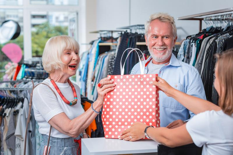 Optimistisch bejaard paar die dankbaarheid voor aardige aankoop uitdrukken stock afbeeldingen