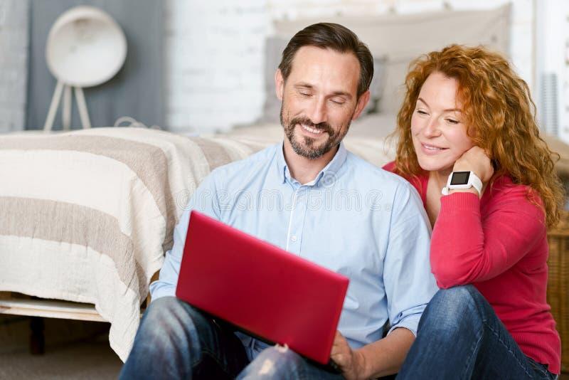 Optimistisch midden oud paar die laptop thuis met behulp van royalty-vrije stock fotografie