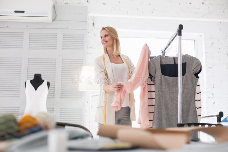 Optimistisch vrouwelijk meer couturier het voorstellen kledingstuk royalty-vrije stock foto's