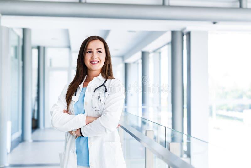 Optimistische Ärztin, die am Krankenhaus Innen aufwirft stockbilder