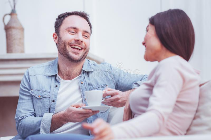 Optimistische gebaarde mens die ruim terwijl het spreken met zijn vrouw glimlachen royalty-vrije stock afbeeldingen