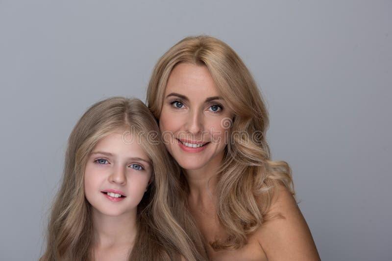 Optimistische hübsche Frau und kleines Mädchen drücken Freude aus lizenzfreies stockbild