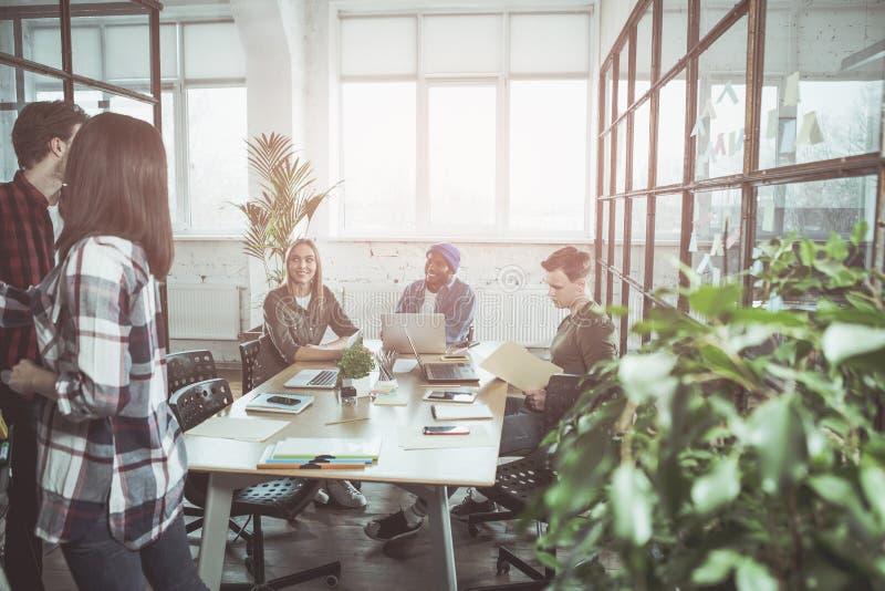 Optimistische Mitarbeiter bearbeiten im Büro stockfotografie