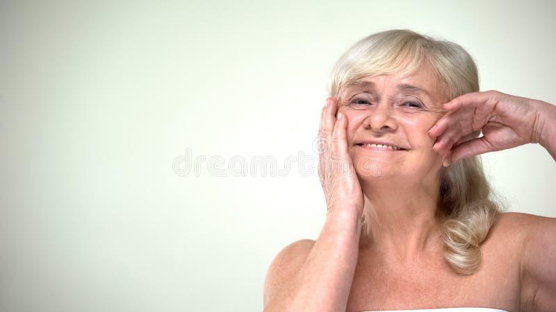 Optimistische nette Dame, die das l?chelnde Gesicht, skincare, positive Lebenhaltung streicht stockbilder