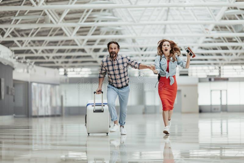 Optimistischer Mann und Mädchen, die mit Gepäck läuft stockbilder