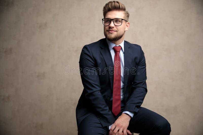 Optimistischer weg schauender und lächelnder Geschäftsmann lizenzfreies stockbild