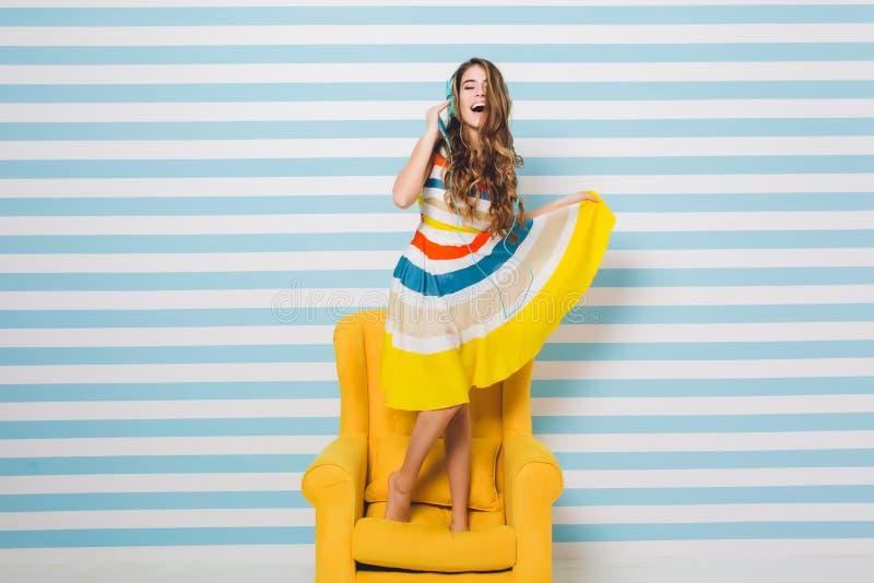 Optimistisches M?dchen, das buntes Kleid tn k?hlt im gelben Lehnsessel und in h?render Entspannungsmusik und tanzt mit tr?gt lizenzfreies stockbild
