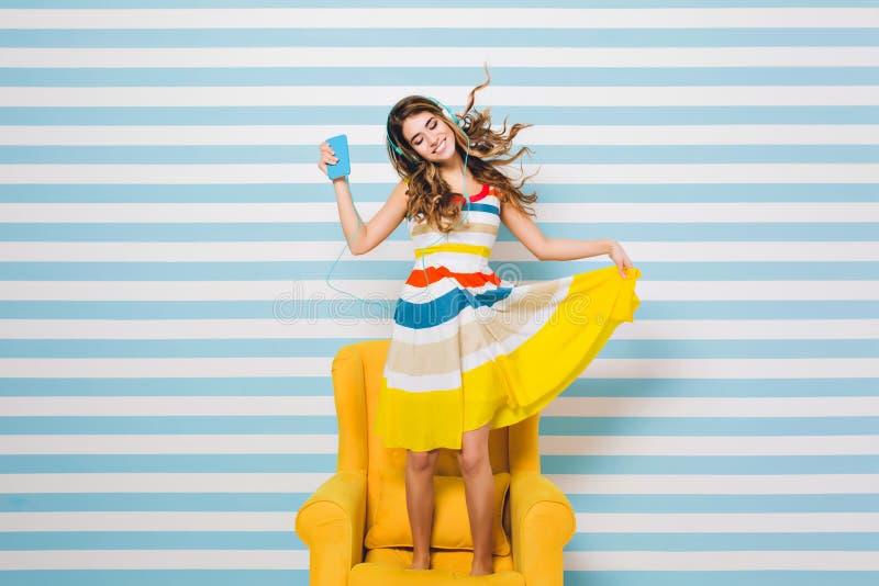 Optimistisches M?dchen, das buntes Kleid tn k?hlt im gelben Lehnsessel und in h?render Entspannungsmusik und tanzt mit tr?gt stockbild