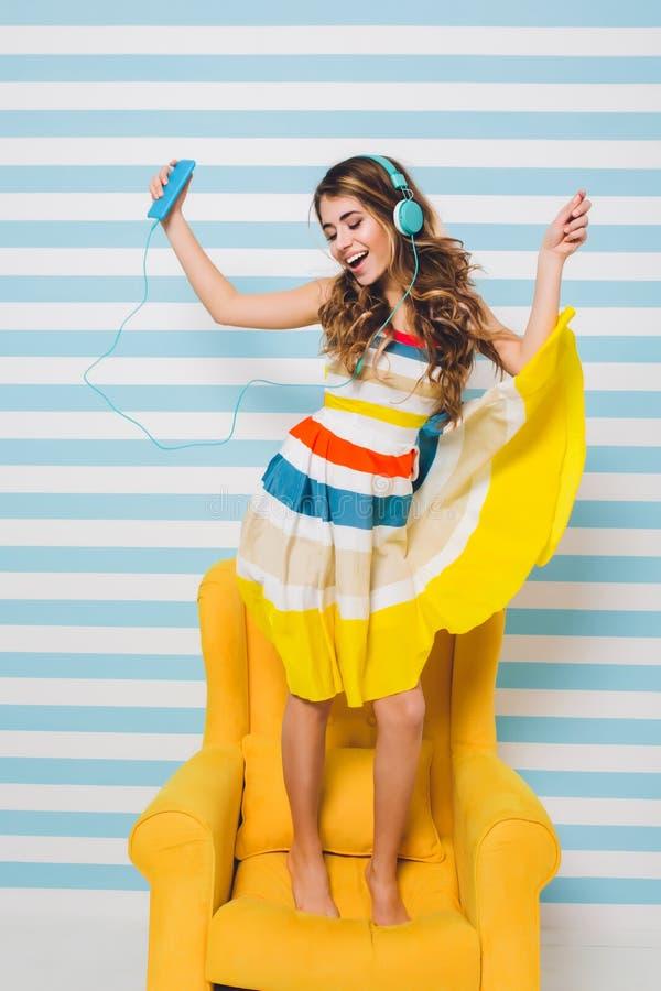 Optimistisches M?dchen, das buntes Kleid tn k?hlt im gelben Lehnsessel und in h?render Entspannungsmusik und tanzt mit tr?gt stockfotos