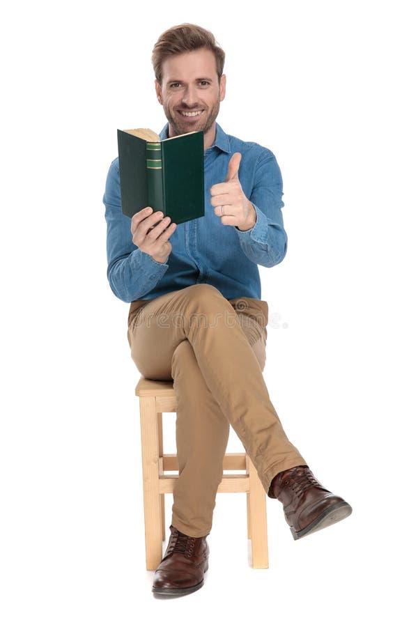 Optimistisk grabb som ger upp en tumme och rymmer en bok royaltyfria bilder