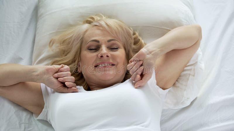 Optimistisk medelålders kvinna som vaknar upp tidigt i morgon, vitalitet och energi arkivbild