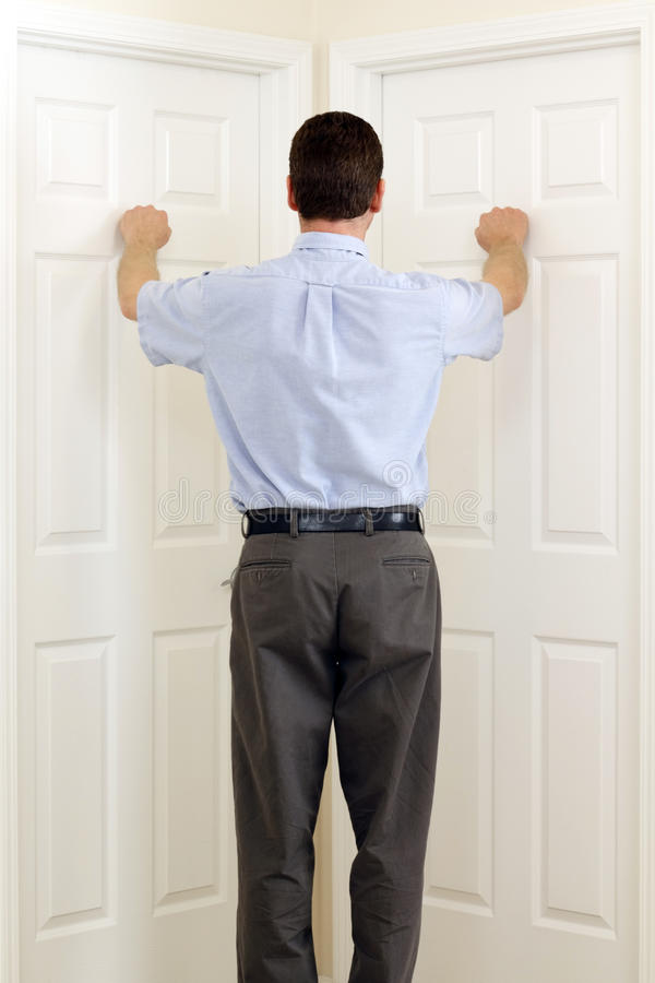 Options. Man knocking on two doors that are side by side at the same time stock image